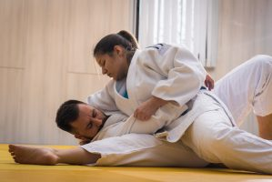 Young woman and man judo fighters in sport hall